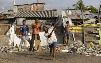 Boys play a game of cricket on a patch of ground near the R Premadasa Stadium in Colombo