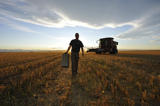 A worker carries an air filter during wheat harvest on the Stephen and Brian Vandervalk farm near Fort MacLeod