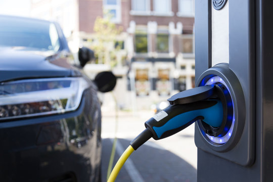 View of an Electric Car Charging Column and in the background a partial view of a car