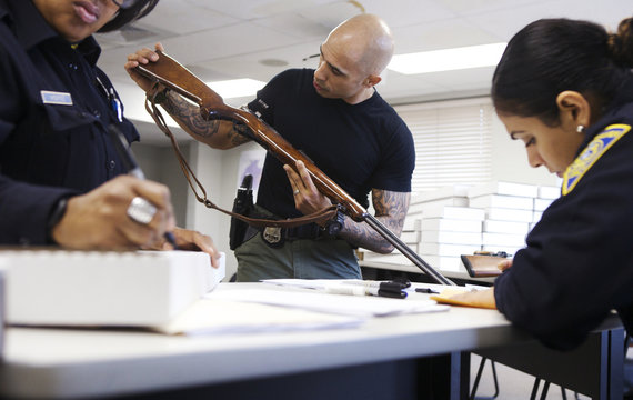 A police officer inspects a 22 caliber long rifle during a gun buyback event in New Haven