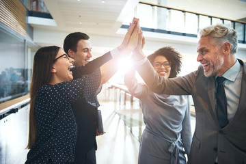 Laughing multiethnic team giving high five in office