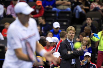 U.S. team captain Courier watches as John Isner practises before his match against Brazil's Bellucci during the Davis Cup world group first round tennis tournament in Jacksonville