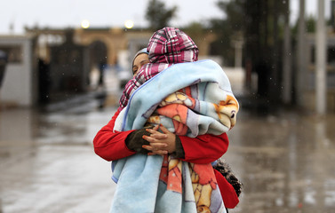 A Tunisian woman holds her child as she crosses the border into Tunisia at the border crossing of Ras Jdir after fleeing unrest in Libya