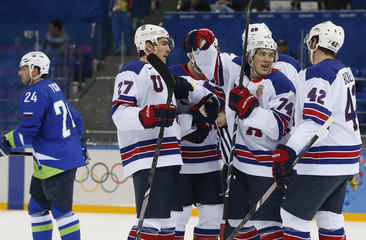Team USA's Oshie celebrates with teammates after Mcdonagh's goal as Slovenia's Ticar skates away  during second period of their men's preliminary round ice hockey game at the 2014 Sochi Winter Olympics