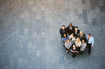 Multiracial business people standing in office hall and looking up