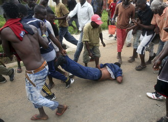 Protesters drag a female police officer accused of shooting a protestor in the Buterere neighbourhood of Bujumbura