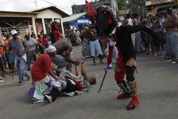 A man dressed up as the devil prepares to 'torture' a pedestrian during the Congos and Devils celebration in Nombre de Dios