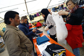 Migrants look for donated clothes at an improvised temporary shelter in a sports hall in Hanau