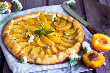 Homemade galette with nectarine peach on rustic wooden background. Top view, Horizontal