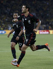 Mexico's Rafael Marquez  celebrates his goal with team mate Giovani dos Santos    during the 2010 World Cup opening match against South Africa at Soccer City stadium in Johannesburg