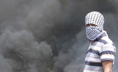 A masked Palestinian protester stands near burning tyres during clashes with Israeli soldiers, following a protest, in Kofr Qadom near Nablus
