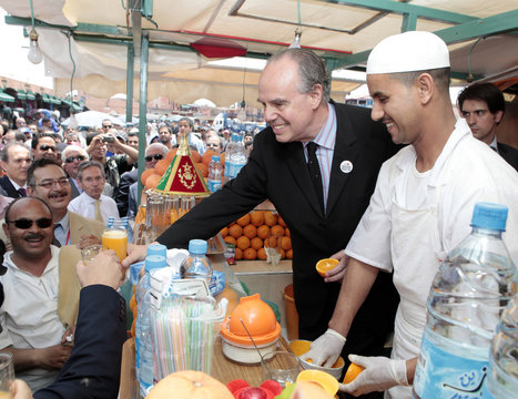 French Culture Minister Frederic Mitterrand has a drink with orange juice merchants in Marrakesh