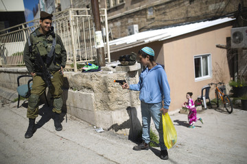 An Israeli soldier looks at a Jewish settler youth as he plays with a toy gun during a parade marking Purim in Hebron
