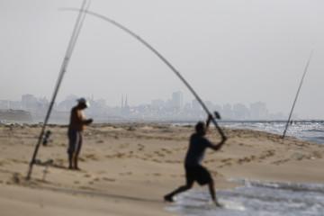 Israeli fishermen are seen on Zikim beach on the Mediterranean sea as the northern Gaza Strip is seen in the background