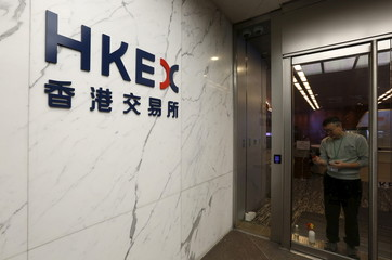 A worker removes old logos on the glass door as a new one is dispalyed at an entrance to the Hong Kong Exchanges Hong Kong