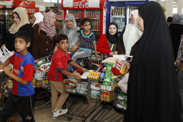 People with their trolleys shop at the Civil Service Consumer Corporation in Amman, in preparation for Ramadan