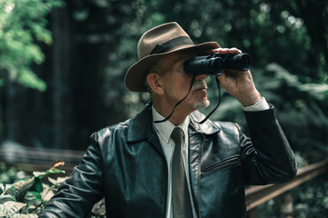 Explorer with hat in jungle looking through binoculars.
