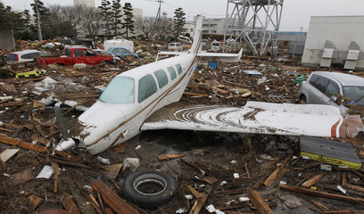 Wreckages of cars and an airplane are seen at a devastated area after an earthquake and tsunami near Sendai airport in northern Japan