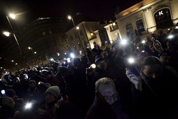People use flashlight and mobiles to protest against new legislation to increase the government's surveillance powers in front of the Presidential Palce in Warsaw