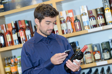 Man holding bottle of wine and a smartphone