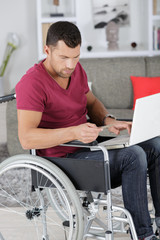 disabled man in wheelchair typing on laptop