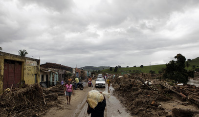 Residents leave their houses after heavy rains in Uniao dos Palmares