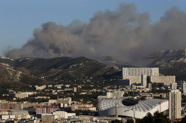 The Velodrome stadium in Marseille is seen as smoke fills the sky during fires which burn the Calanques National Park