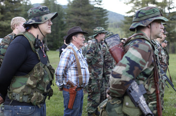Lewis Beebe of the 17th battalion, and other members of the Light Foot Militia from Idaho and Washington stand to attention during an annual gathering near Priest River