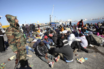 Migrants from sub-Saharan Africa await processing in the port of Tripoli after attempting to cross the Mediterranean Sea to Europe