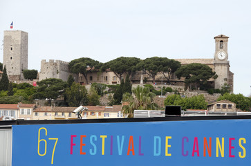 A security camera is seen above a poster of the 67th Cannes Film Festival near the Port of Cannes with in the background the Suquet, old city area of Cannes