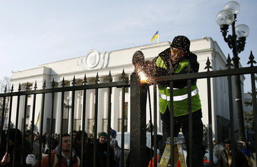 A member of a self-defence unit saws a fence enclosing the parliament building in Kiev