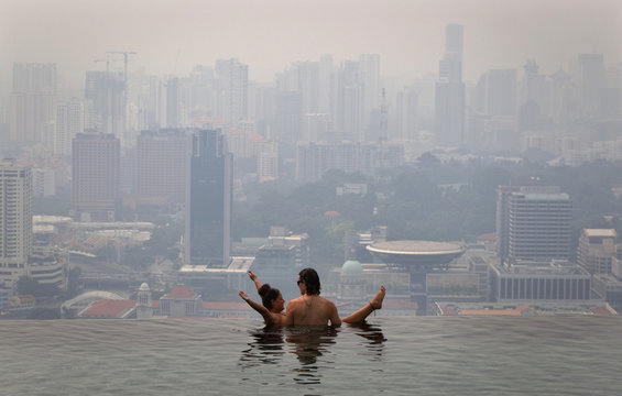 A couple relaxes in an infinity pool overlooking the haze-covered skyline in Singapore