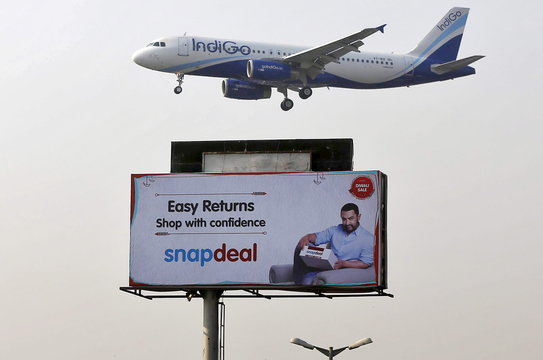 IndiGo Airlines aircraft flies above an advertisement of Indian online marketplace Snapdeal, in Mumbai, India