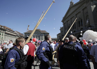 Swiss riot police patrol among the members and supporters of the Swiss People's Party on the Federal Square in Bern