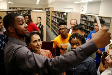 Myanmar's Suu Kyi takes selfies with students after meeting with them on a visit to Roosevelt High School in Washington, U.S.