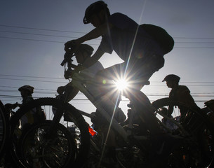 Cyclists are silhouetted as they pedal during the 14th Tour of the Fireflies, an environmental advocacy event, along a street in Pasig City, Metro Manila