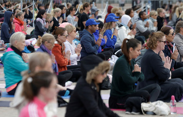 Hundreds participate in a mass yoga event in front of the Sydney Opera House on World Yoga Day in Sydney