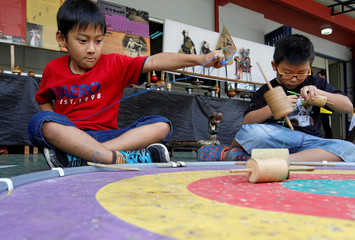 Boys play with spinning tops during an event for traditional games at a school in Jakarta