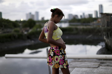 File photo of Eritania Maria, who is six months pregnant, is seen in front of her house at a slum in Recife