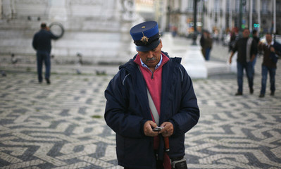 A member of the Portuguese National Republican Guard checks his phone before a protest against austerity measures in Lisbon