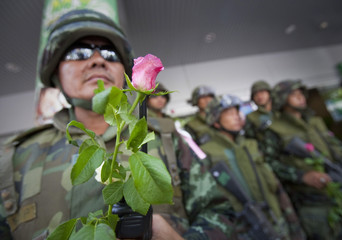 A Thai army soldier holds a pink rose given to him by members of Thailand's Finance Minister Korn Chatikavanij's entourage in Bangkok