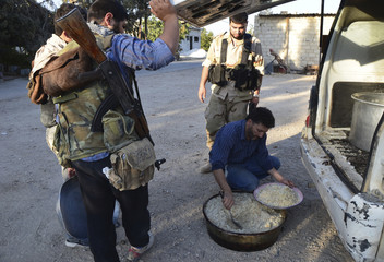 A Free Syrian Army fighter prepares food in the eastern al-Ghouta, near Damascus