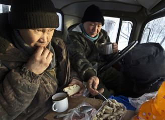 Lumberjacks Alexey Egorov, 45, and Semion VInokurov, 53, eat lunch in the cabin of their truck in the forest outside Tomtor
