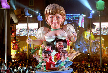 A float which portays German Chancellor Angela Merkel makes it way through the crowd during the Carnival parade in Nice