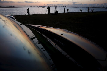 People prepare to take photos of a partial solar eclipse during sunrise amongst shipping vessels in Singapore