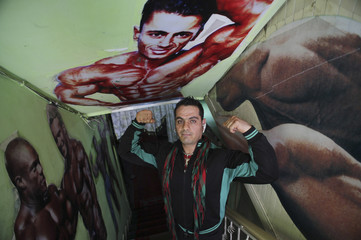 An Afghan bodybuilder and owner of a bodybuilding club poses for a photograph at his club in Kabul