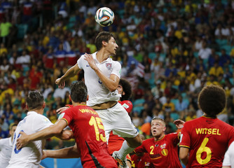 Gonzalez of the U.S. jumps for the ball near Belgium's national soccer players during their 2014 World Cup round of 16 game at the Fonte Nova arena in Salvador