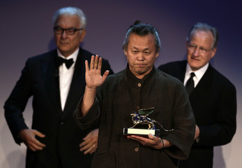 "South Korean director Kim Ki-duk celebrates after receiving the Golden Lion prize for best movie ""Pieta"" at the 69th Venice Film Festival in Venice"