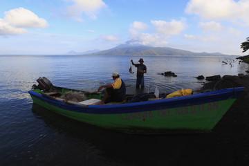 Men fish in the Xolotlan lake, or Lake Managua, in Momotombo town