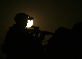 U.S. Marine silhouetted by full moon as he stands guard over security post at base in Marjah district